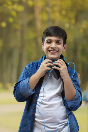 Boy with headphone listing to music on smartphone outdoors