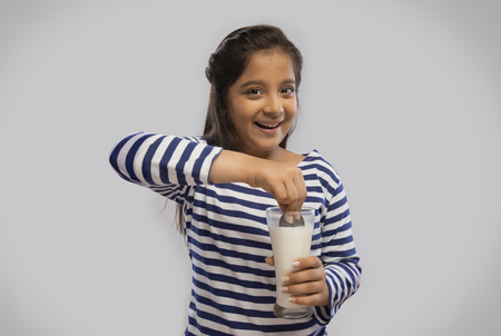 Smiling girl dipping a biscuit in a glass of milk