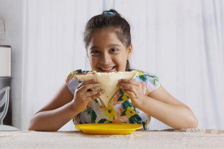 Smiling girl eating a bread sandwich sitting at dining table