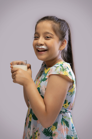 Portrait of a smiling girl with milk moustache drinking milk in a glass