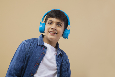 Boy with headphone while listing to music over color background