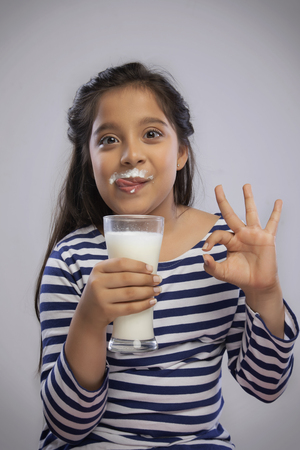 Portrait of a smiling girl with milk moustache holding a glass of milk and making a OK sign with hand