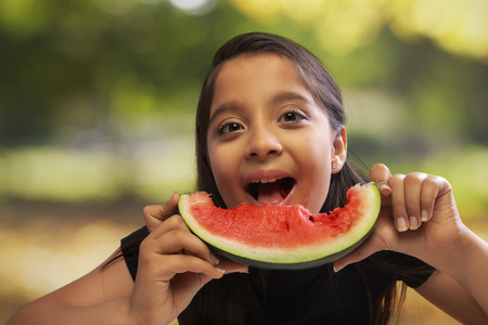Happy girl eating a slice of watermelon holding with both hands