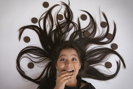 Close up of smiling girl lying on floor eating biscuit with her hair arranged in a tree design with biscuits