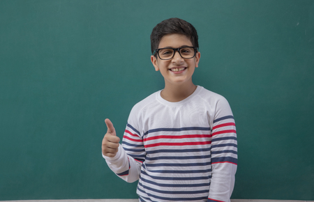 Portrait Of Boy Gesturing Thumbs Up Sign Against Blackboard Stock Photo