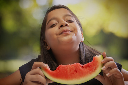 Girl eating a watermelon enjoying its taste with closed eyes