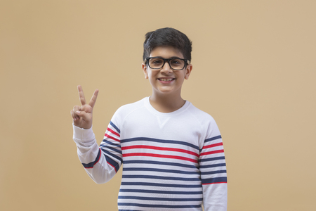 Portrait Of boy showing a victory sign Against color background