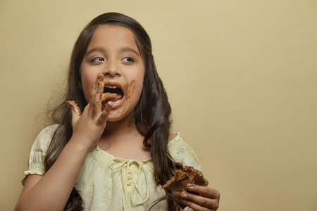 Girl licking chocolate from fingers holding a chocolate bar in the other hand looking away Stock Photo