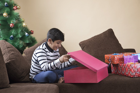 Portrait of a surprised young boy opening a Christmas gift box