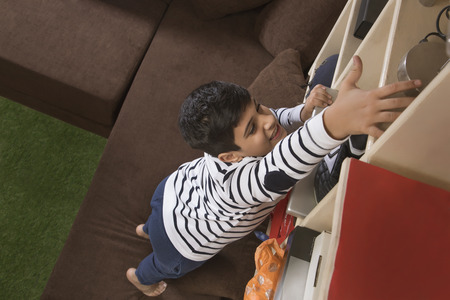 Young boy Reaching Up to Take something From a Bookshelf