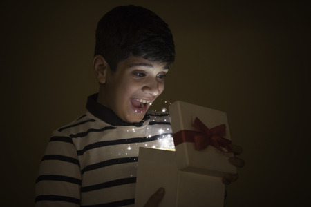 Boy Happy while opening Magic Gift, lights and Stars Stock Photo