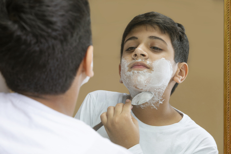 Boy pretending to shave his face Stock Photo