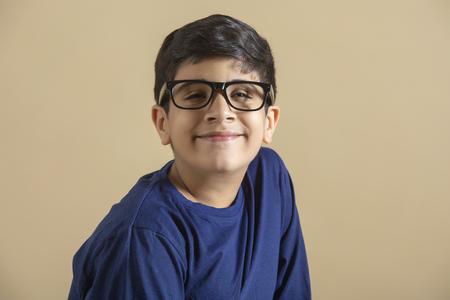 Portrait of smiling teenage boy, wearing glasses