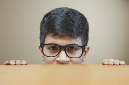 Portrait of peeking boy wearing glasses