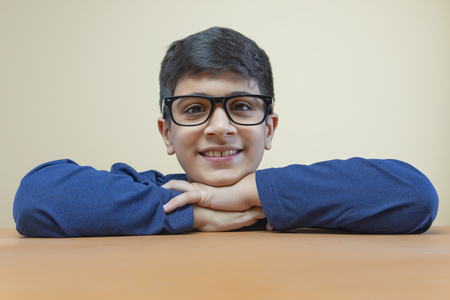 Portrait of boy folded his hands on a table wearing glasses