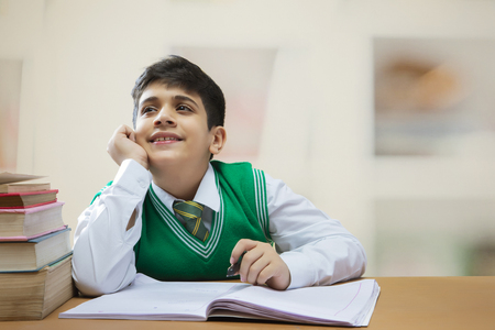 School boy is looking up while studying at class