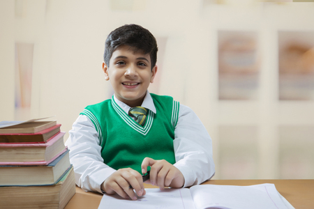 Young schoolboy doing his writing homework on the table Stock Photo