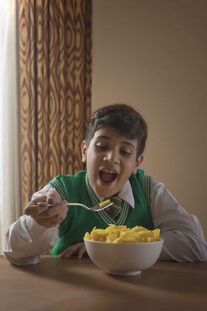 School boy eating macaroni and cheese at home Stock Photo