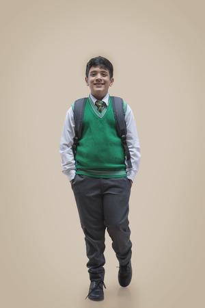 Portrait of schoolboy with hands in pockets over color background Stock Photo