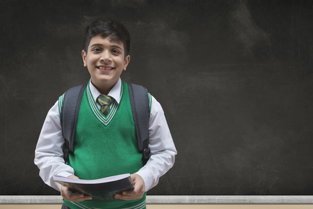 Portrait of a smiling school boy holding books and carrying backpack