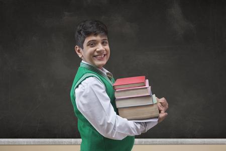 School Boy holding various books against big blackboard