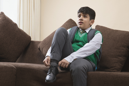 School Boy tying shoes at home Stock Photo