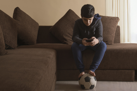 Young Boy sitting on sofa using mobile phone Stock Photo