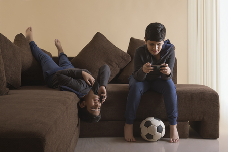 Boys using mobile phones on sofa