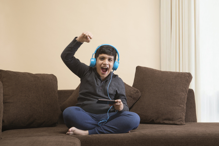 Boy smiling while listening to music with headphones on sofa Stock Photo