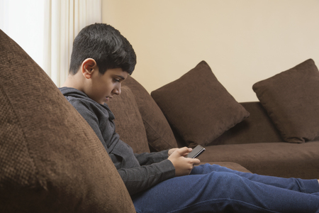 Boy sitting on sofa using smart phone in living room