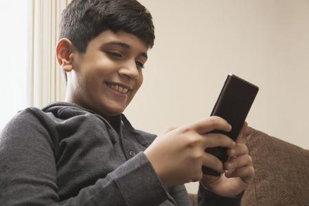 Boy sitting on sofa using Smart phone in living room Stock Photo