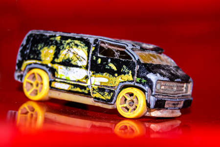 black and yellow mini van toy with red background