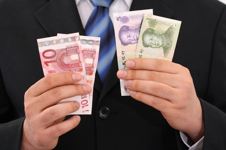 businessman holding yuan and euro in his hands photo