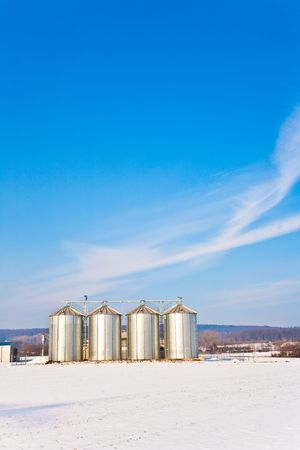 beautiful landscape with silo and snow white acre with blue sky photo
