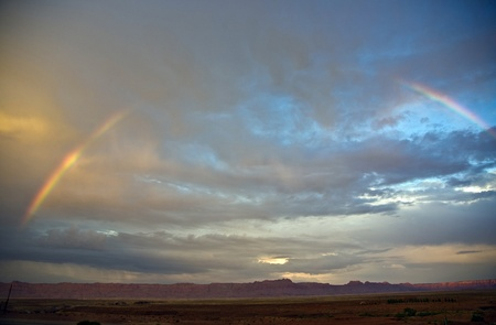 Echo Cliffs with dramatic sky at sunset near Great Canyon with rainbow