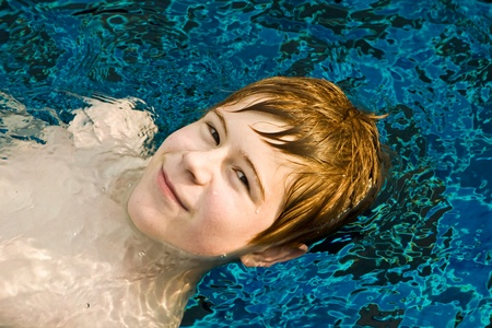 boy is sminning in a pool and enjoying the water, he looks relaxed Stock Photo - 9163187