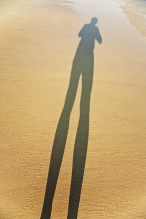 long body shadow of a man in the fine sand of the beach, feet is visible photo