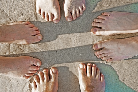 feet of a family in the fine sand of the beached, grouped in a circle photo