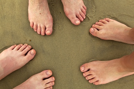 outerbanks: feet of family standing together at beach Stock Photo