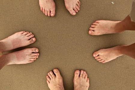feet of family standing together at beach photo