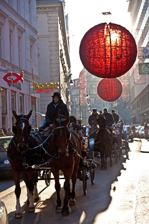 VIENNA, AUSTRIA - NOVEMBER 26: fiaker with tourists passes the decorated streets in the first district decorated with red christmas ball ornament  on November 26, 2010 in Vienna, Austria. photo