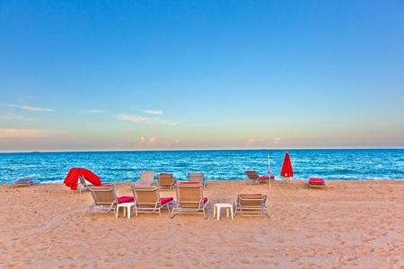 divan: camas div�n rojo en luz puesta del sol en la playa Foto de archivo