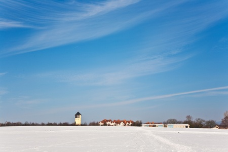 beautiful landscape with water tower and housing area in winter and blue sky photo