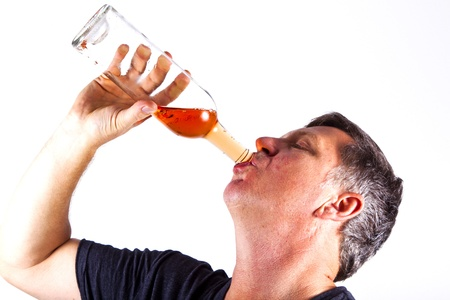 man drinking alcohol out of a bottle photo
