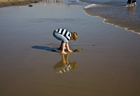 boy at the beach in Venice with reflecting picture in wet sand photo