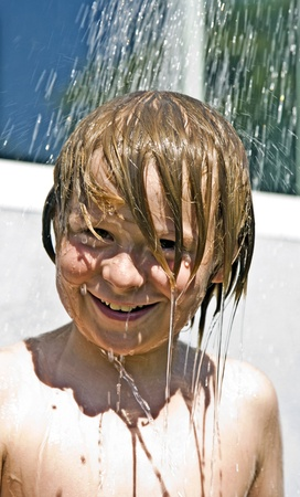 child has a refreshing shower in the heat photo