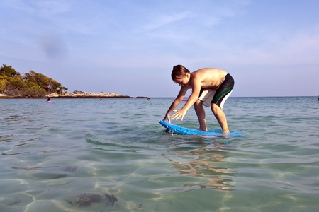 boy is surfing on a small surfboard in a beautiful sea with crystal clear water and blue sky, his brother holds the surfboard on his back photo