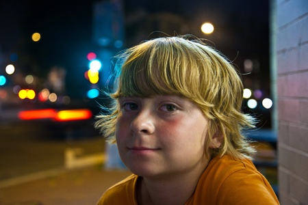 cute boy smiles tired while sitting outside by night next to the street Stock Photo - 9222630