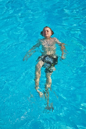 smiling child has fun in the pool photo