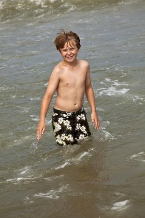 portrait of happy boy enjoying the clear ocean photo